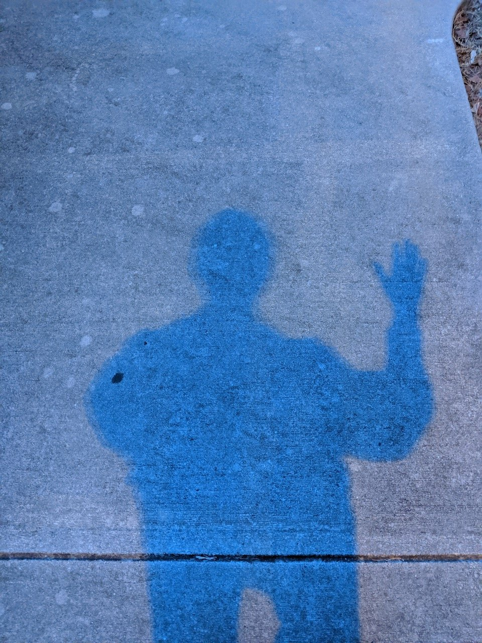 Shadow of standing figure with one arm raised as if waving hello
